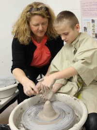Mrs. McKinnon helps with ceramics project